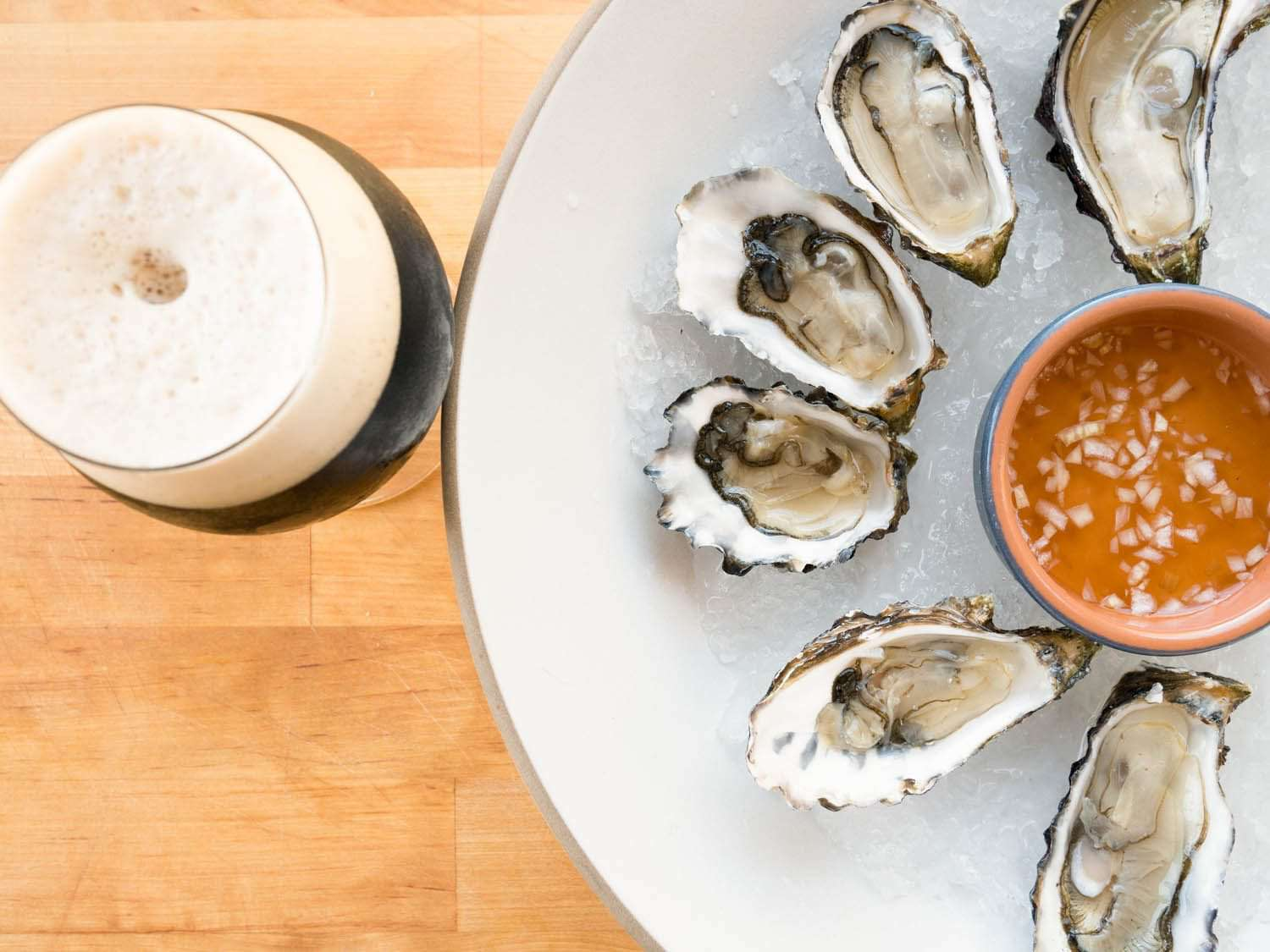 Raw oysters on the half shell with mignonette, served with a beer.