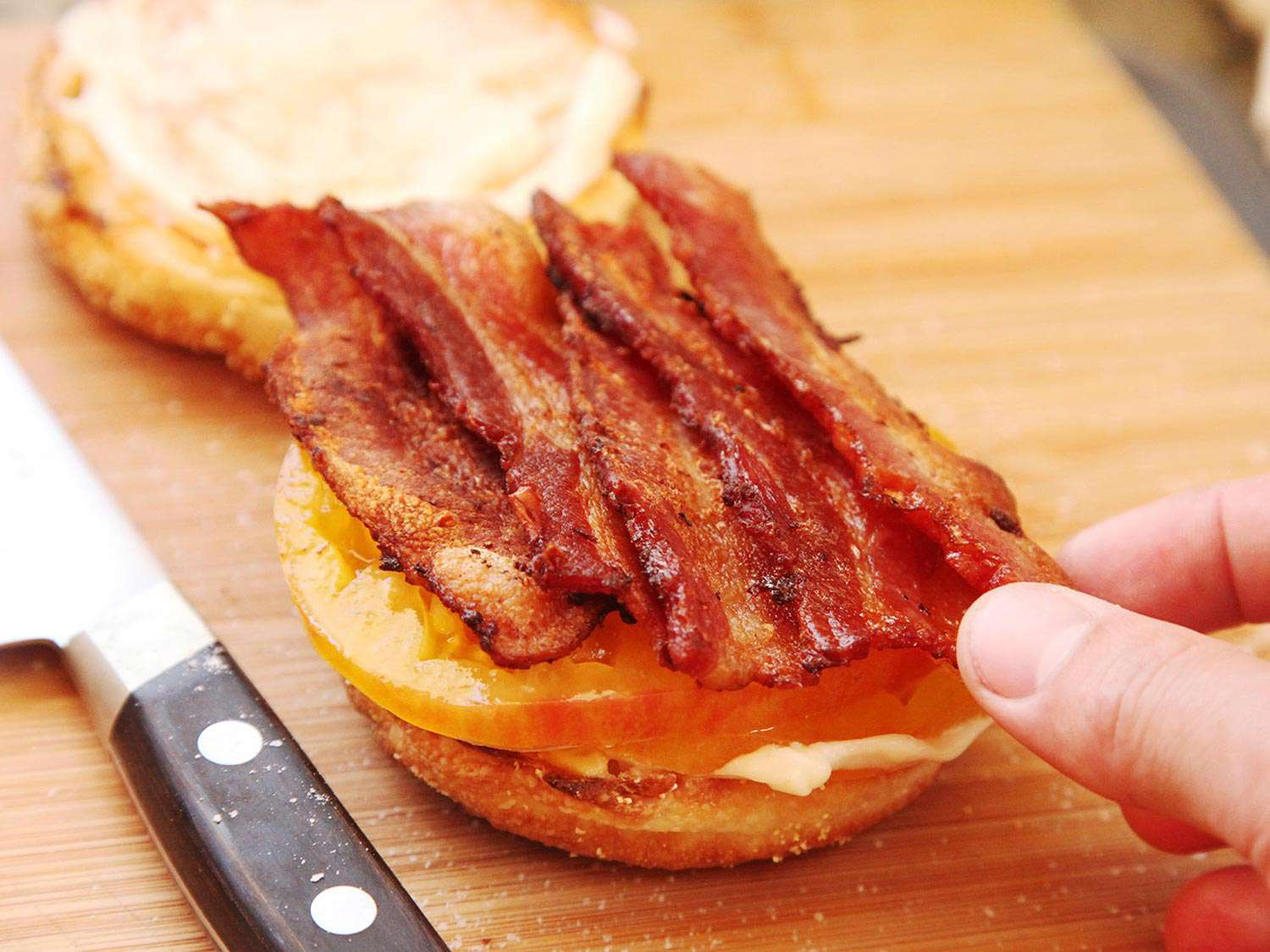 Laying bacon strips on top of tomato and mayo on a toasted English muffin half