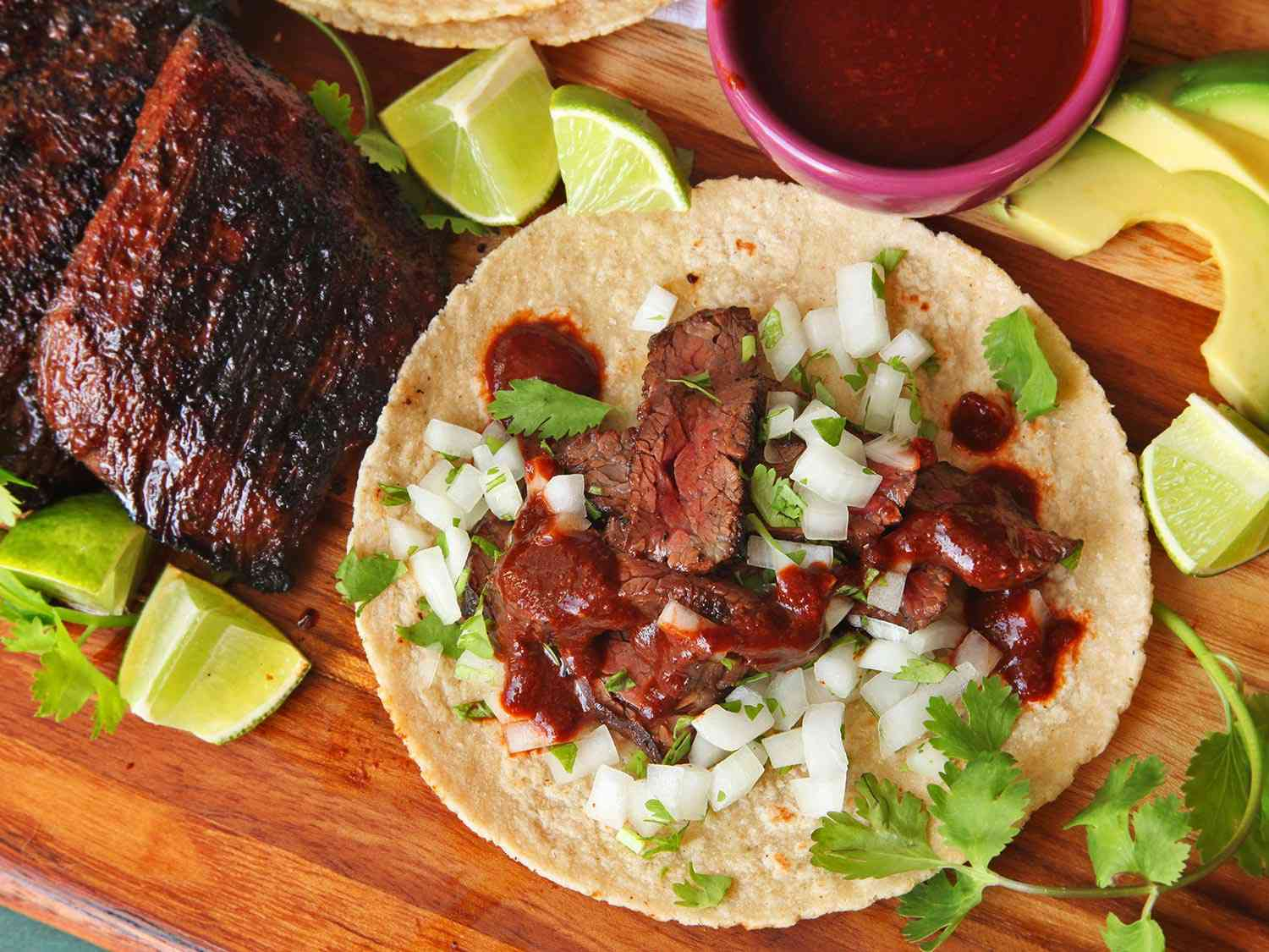 A carne asada taco, made with grilled skirt steak, on a wooden cutting board with additional steak, limes, avocados, cilantro, and salsa surrounding it.