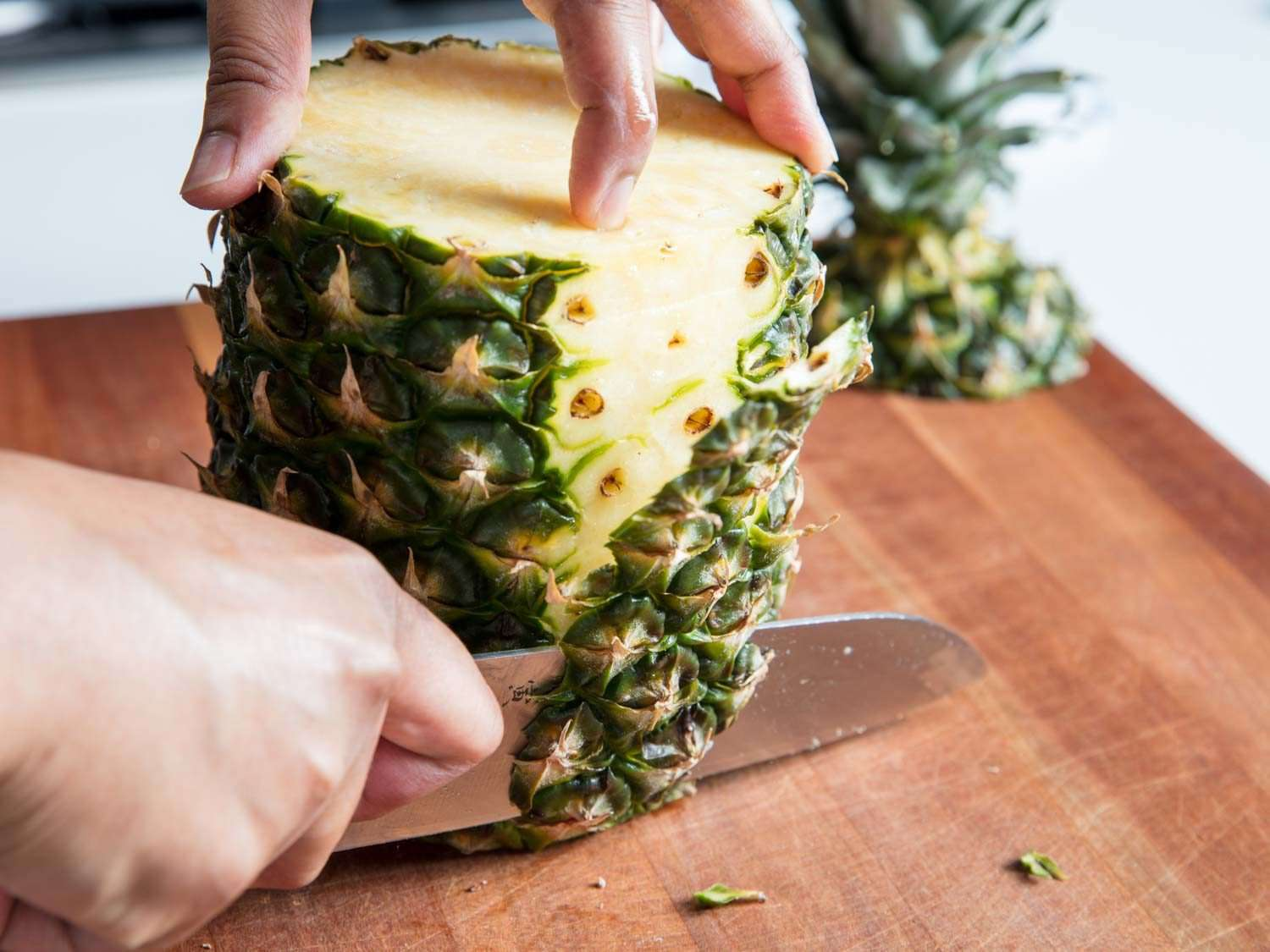 A knife slicing off the sides of a pineapple.