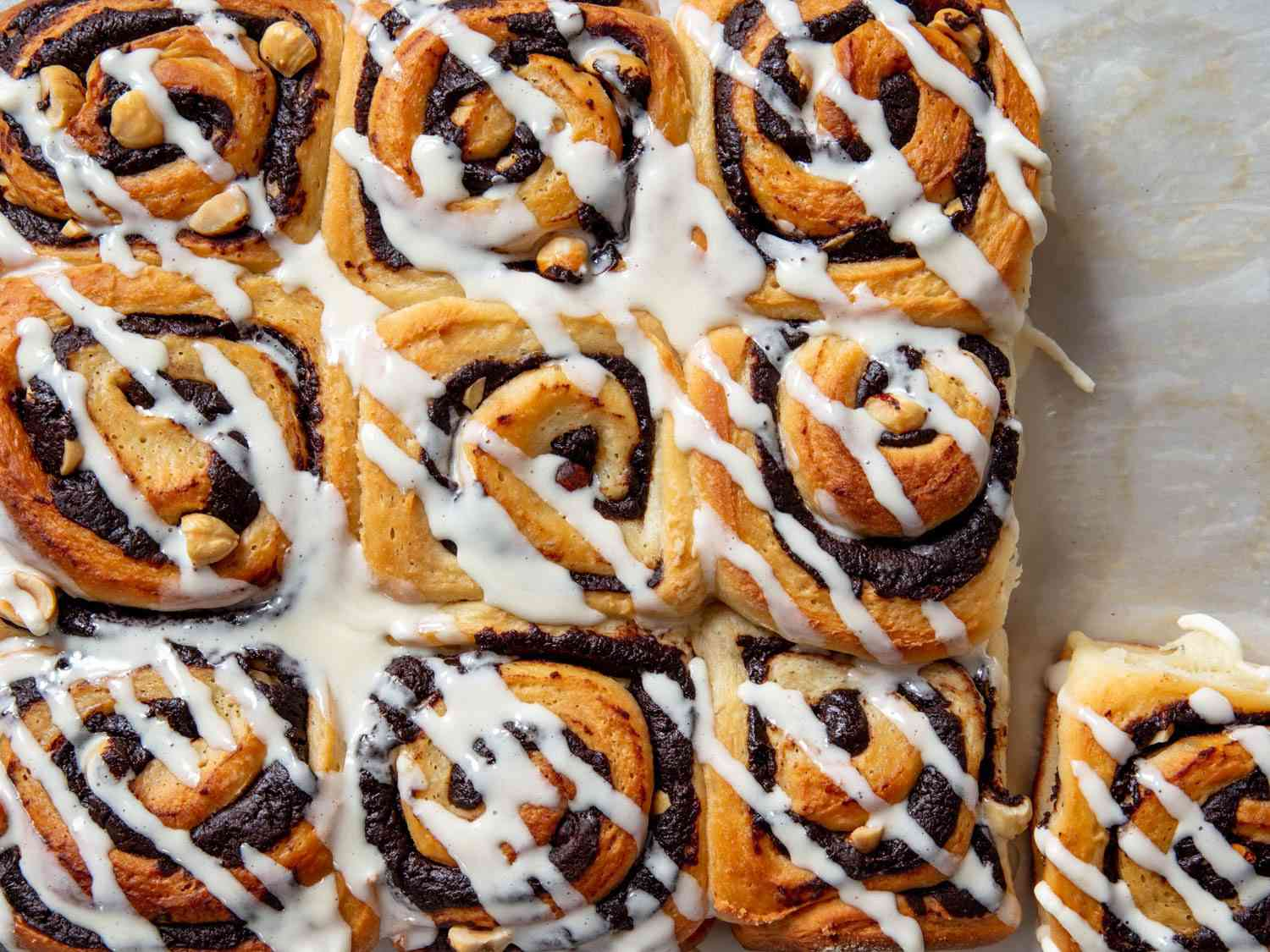 a tray of chocolate hazelnut buns drizzled with frosting