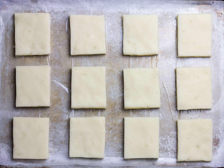 Potato mochi dough cut into identical squares on a baking sheet