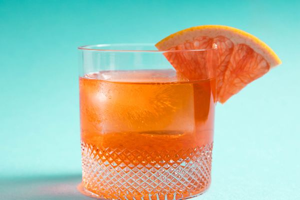 An Unusual Negroni, and Aperol, Lillet, and Gin Cocktail, with a grapefruit wedge on the rim of the glass.
