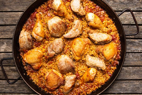 Grilled chicken and pork paella in a paella pan