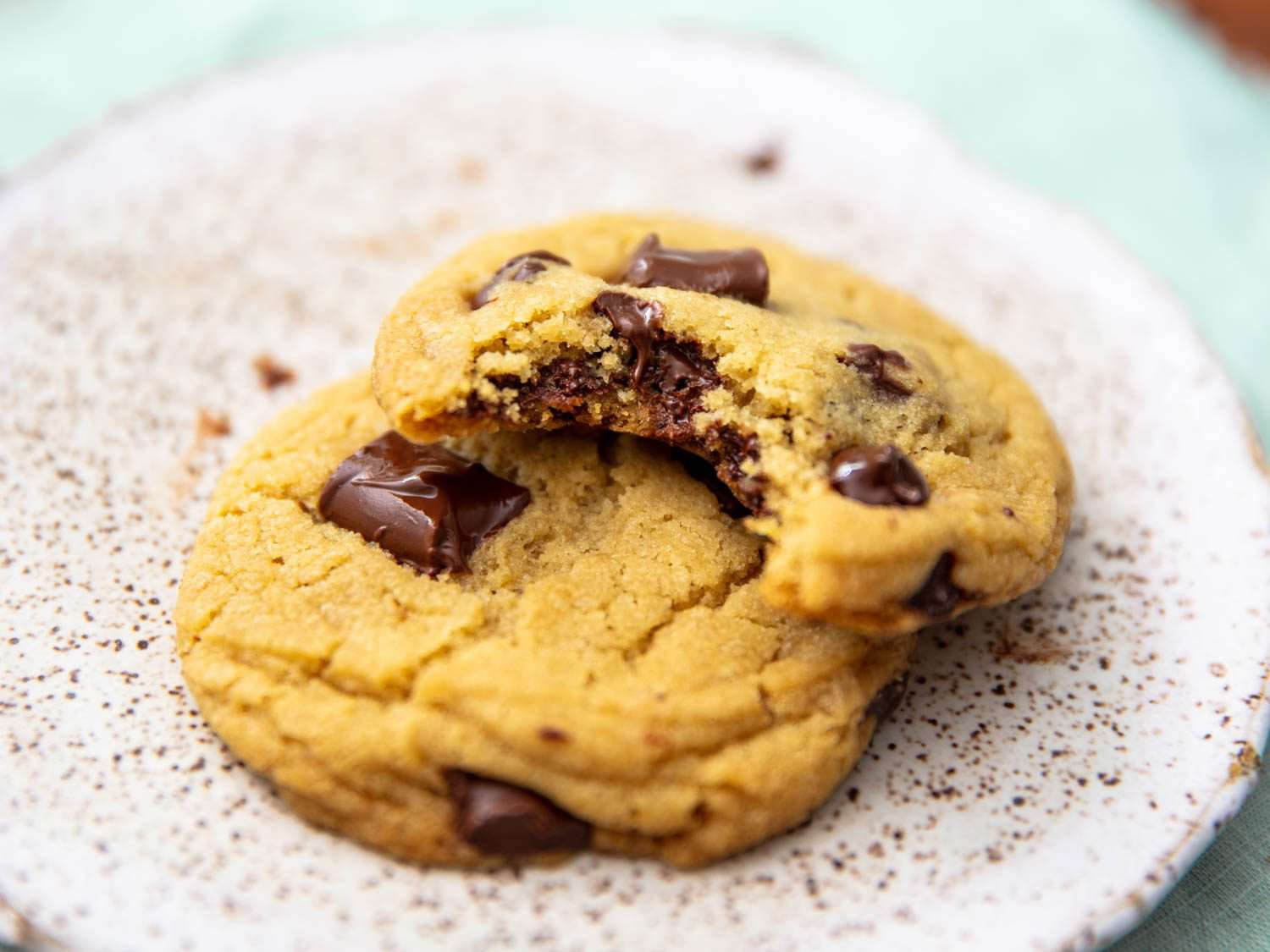 close up of two chocolate chip cookies on a plate, one with a bite missing