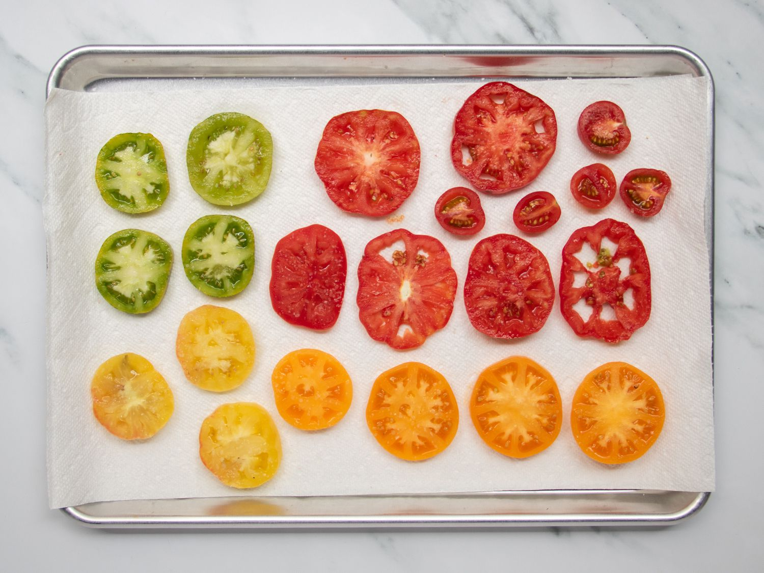 Sliced tomatoes in variety placed on a paper towel-lined rimmed baking sheet