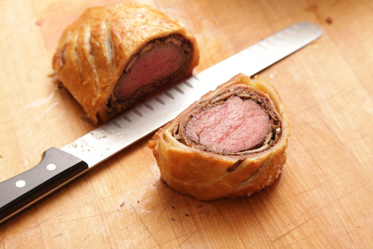 Slicing a perfectly baked beef Wellington on a wooden cutting board with a slicing knife.