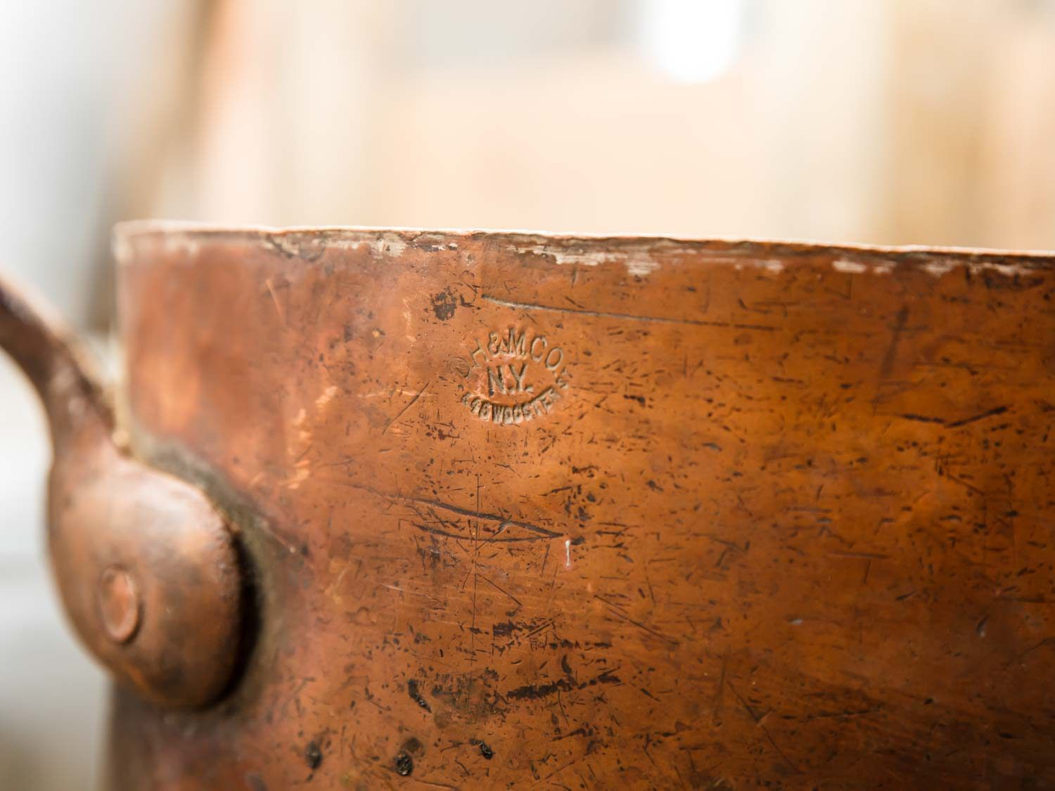 A close-up of the company stamp on a piece of vintage copper cookware