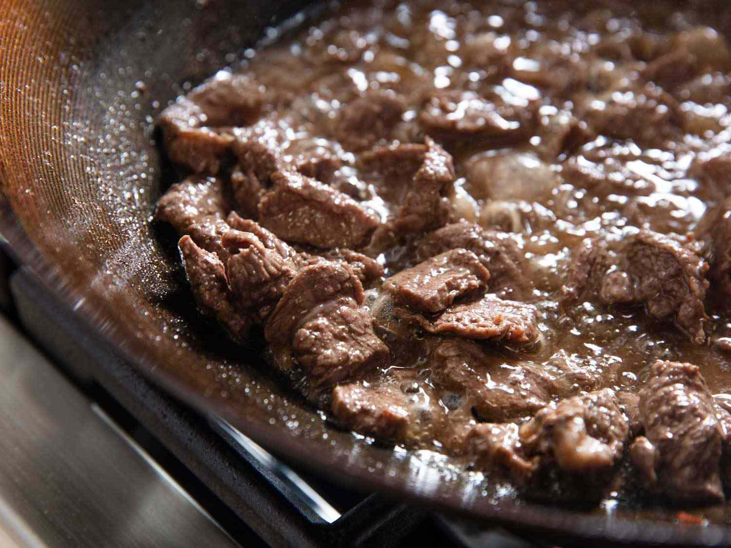Flank steak frying in moderately hot oil in a wok to prepare for dry-frying