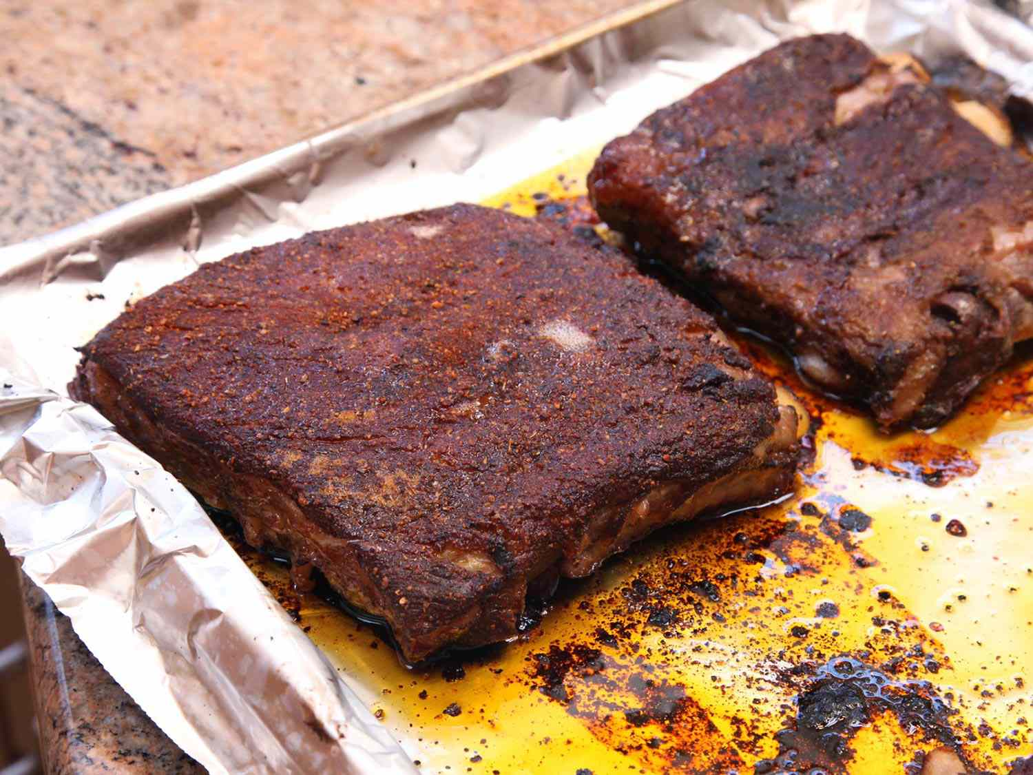 Pork ribs cooked sous vide, coated in dry rub, on a foil-lined baking sheet