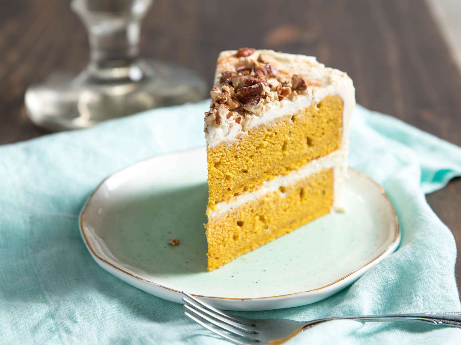 A wedge of pumpkin layer cake with cream cheese buttercream, on a plate