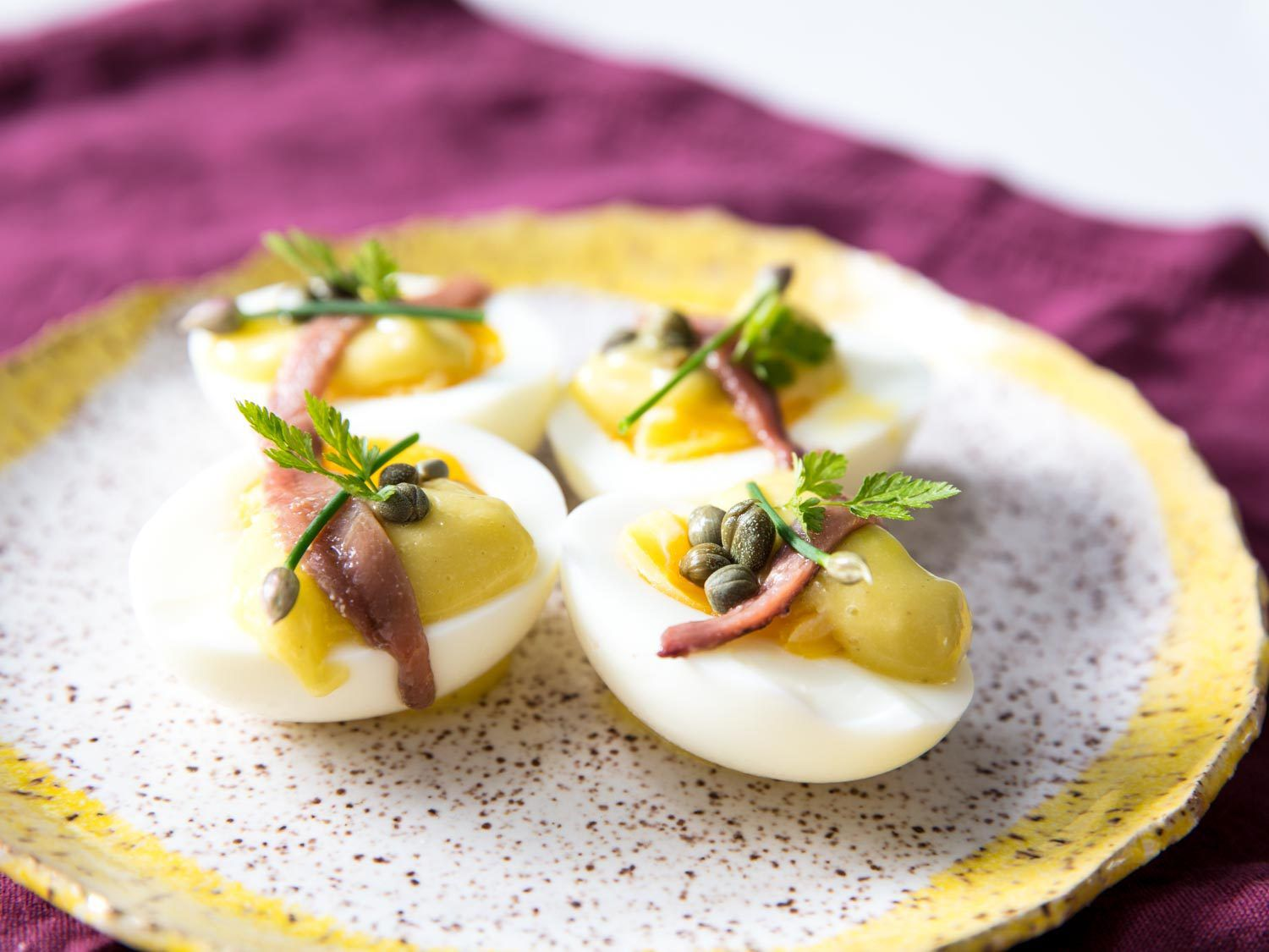 Close-up of four deconstructed deviled egg halves on a plate, topped with anchovy fillets, capers, and homemade mayo