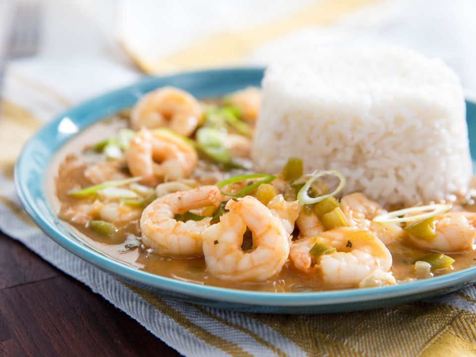 A plate of shrimp étouffée with a mound of steamed white rice.