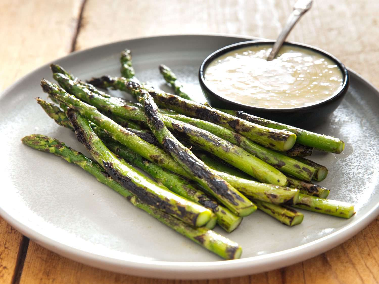 Side view of charred asparagus with a bowl of miso béarnaise.