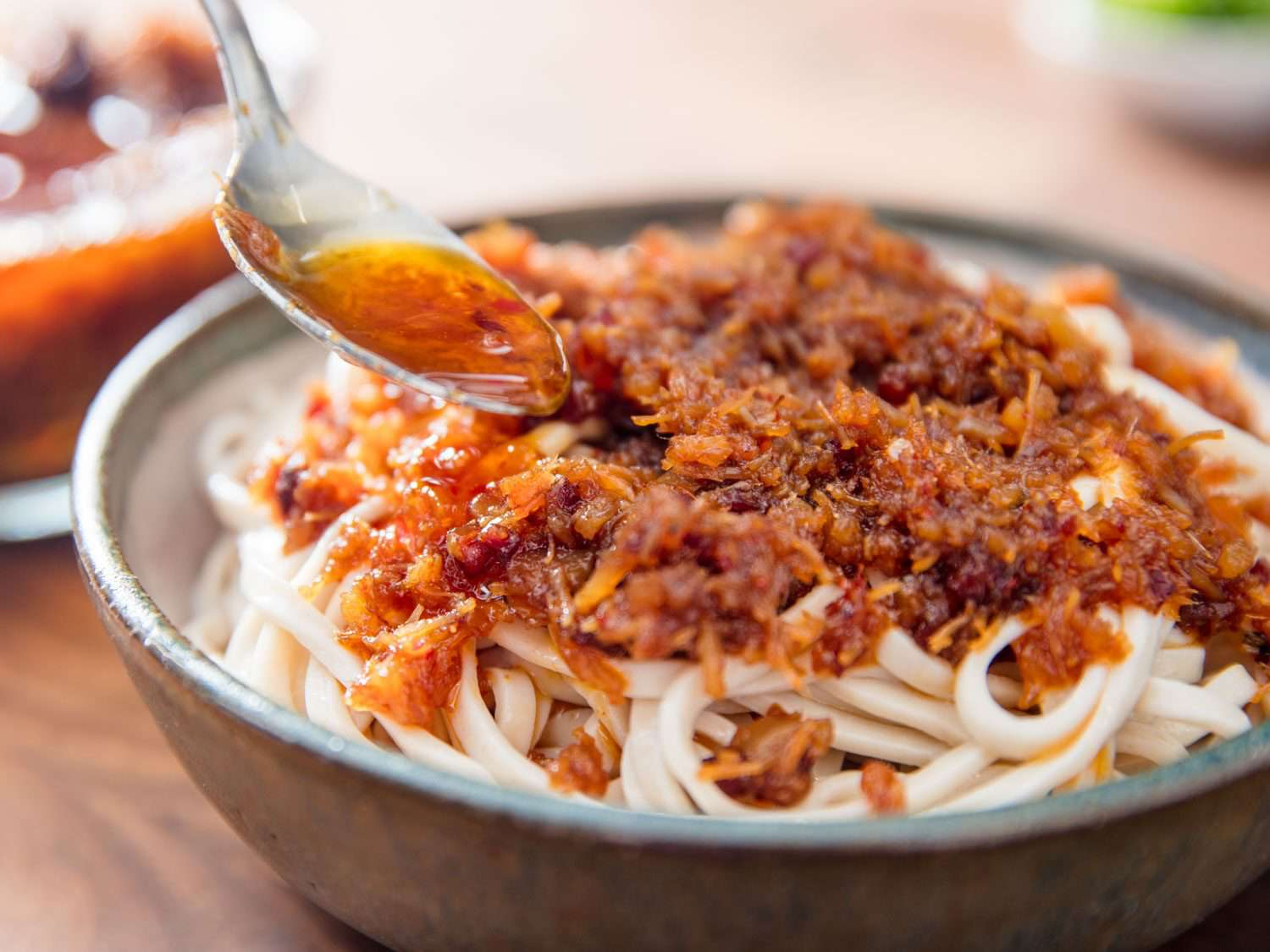 Spooning XO sauce over a bowl of noodles.