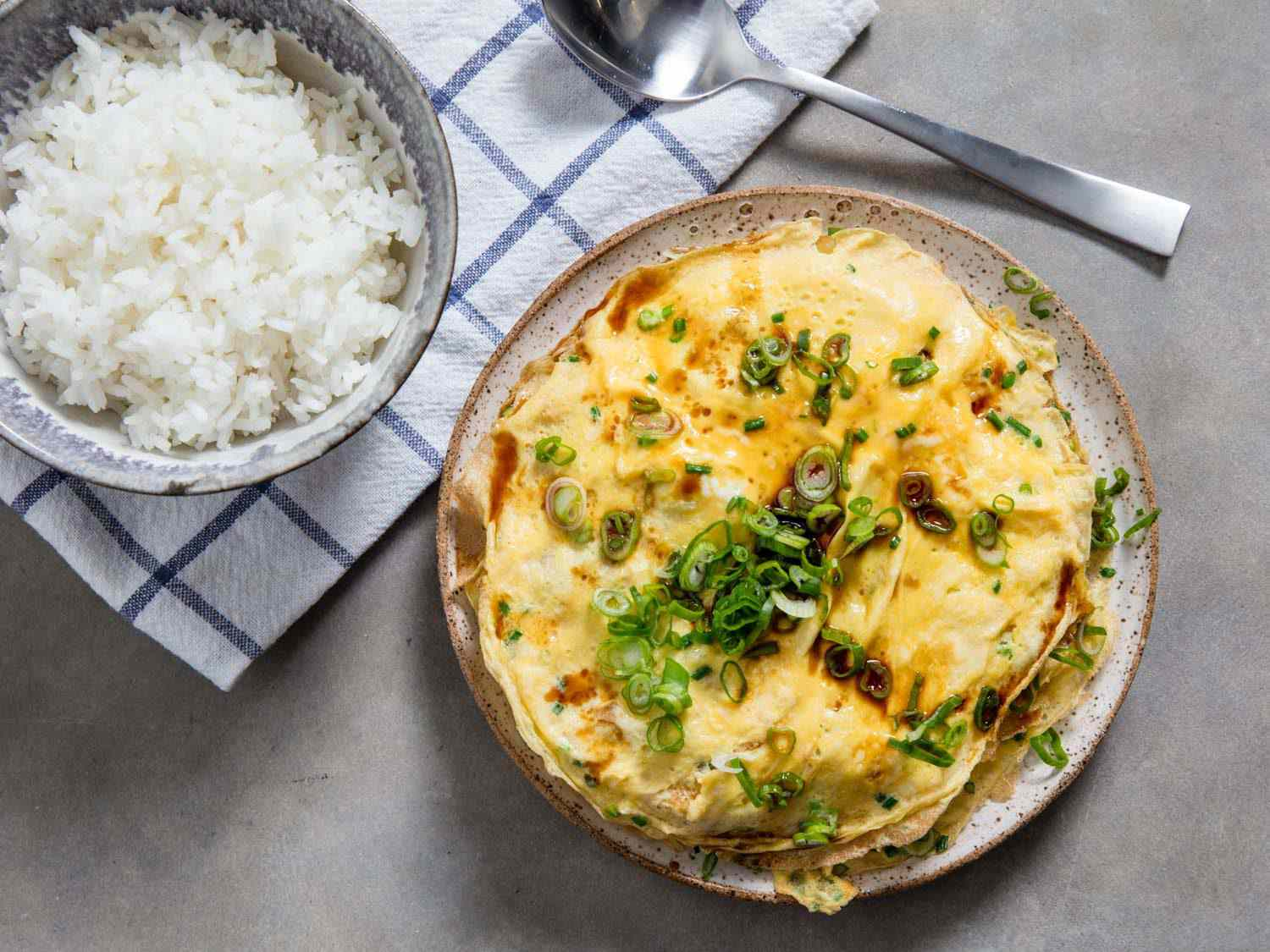Overhead view of Chinese-style layered omelette with bowl of rice alongside