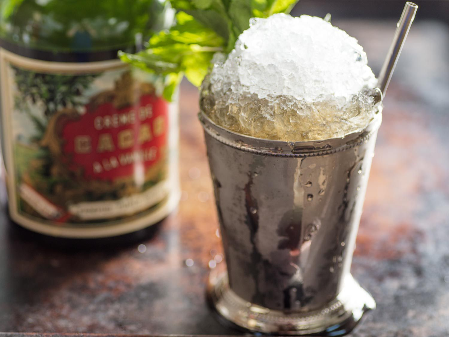A chocolate mint julep in a frosted julep cup, with a bottle of crème de cacao in the background