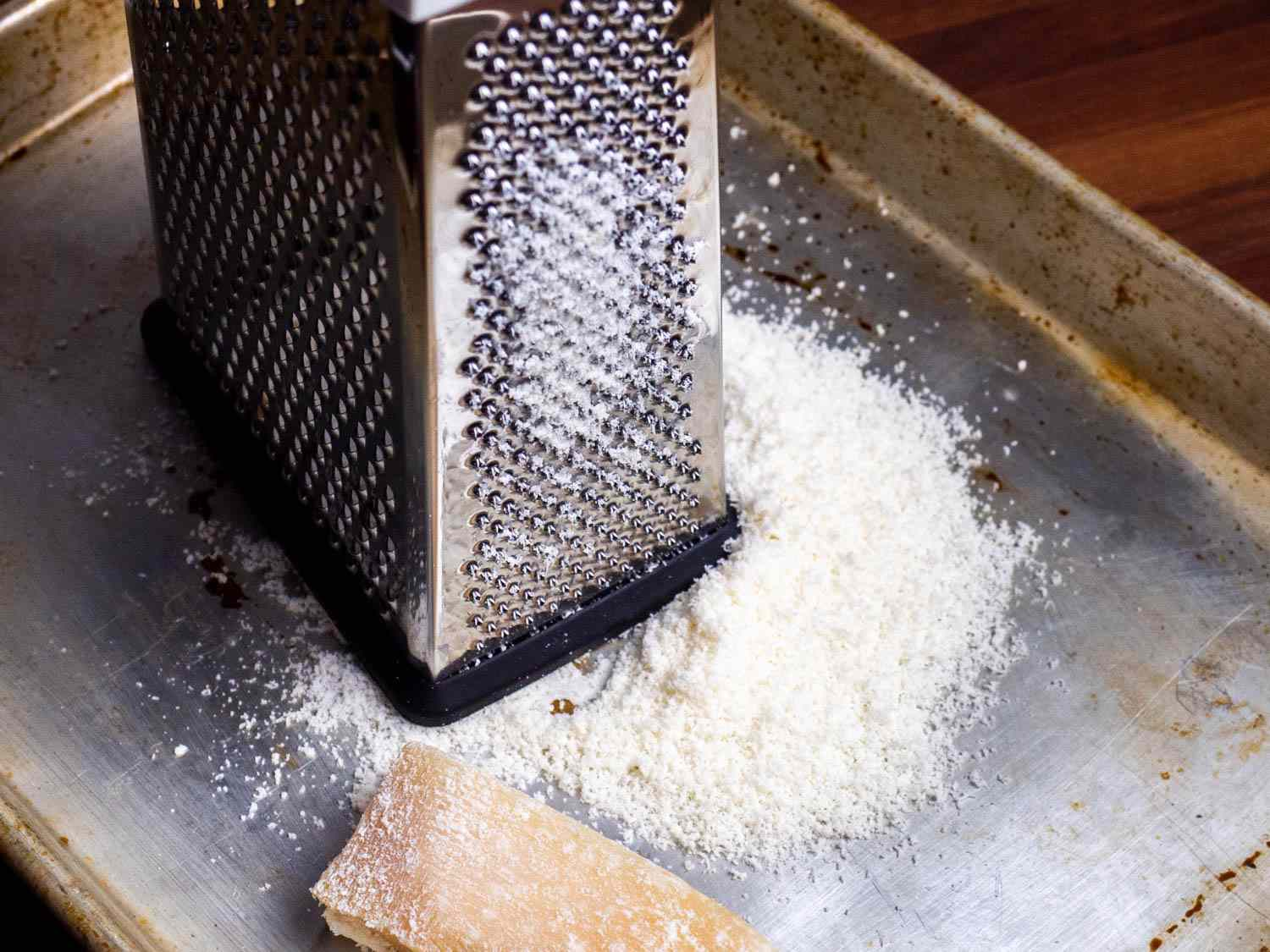 A box grater with a pile of finely grated Parmesan next to it