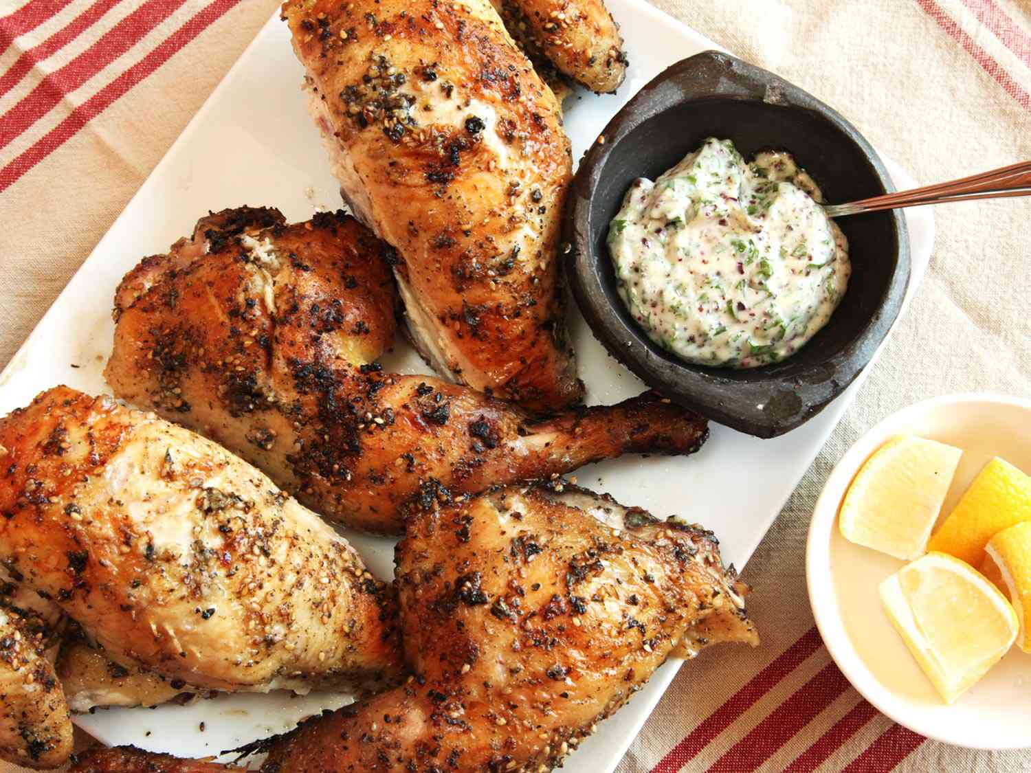 Grilled chicken rubbed with za'atar (Middle Eastern spice blend), next to lemon wedges and a sauce for dipping