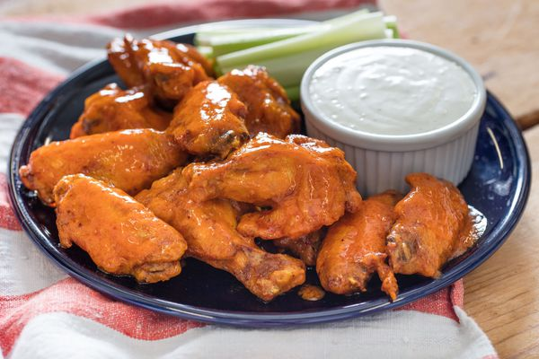 Sous vide Buffalo chicken wings on a blue plate with cup of blue cheese dressing and celery sticks on the side.