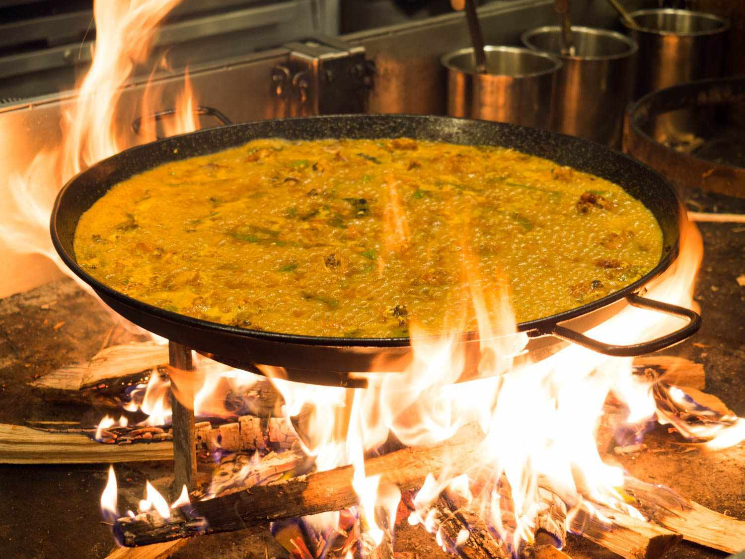A vegetable paella at Mercado Little Spain in NYC, with a blazing wood fire shooting flames up and around the large paella pan. Using thin pieces of wood allows the cook to get a huge fire going very quickly, and then let it die down very quickly as well.