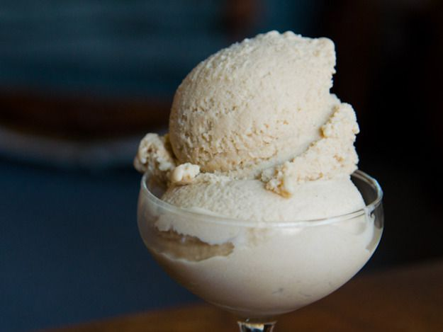 A dish of two scoops of bourbon peach brown sugar ice cream