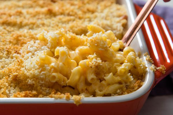 A rectangular casserole dish of macaroni and cheese with breadcrumbs on top.