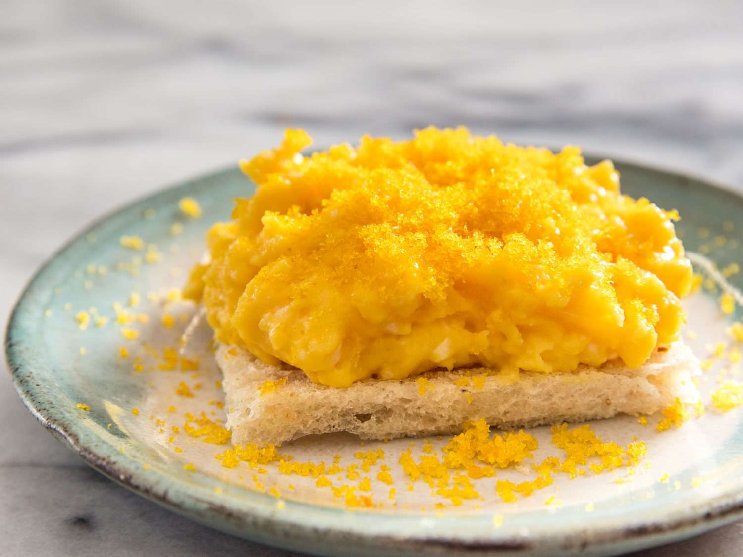 Soft scrambled eggs on toast topped with grated bottarga