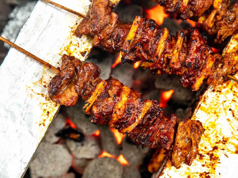 Closeup overhead shot of al pastor skewers grilling directly over hot coals