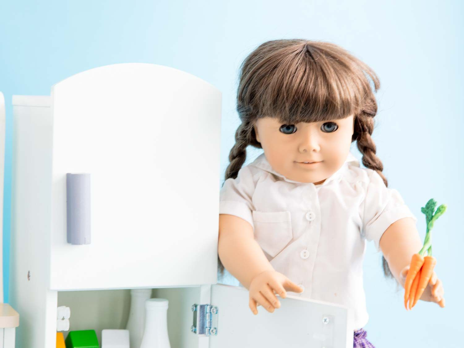 A Molly doll opening a doll-sized white refrigerator, holding a bunch of carrots