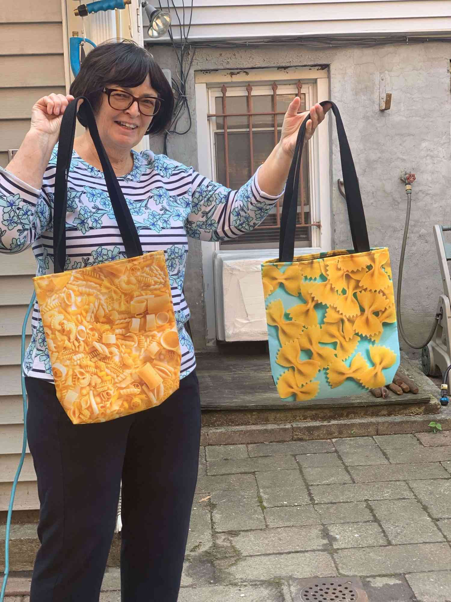 Vicky's mother holding up pasta themed tote bags
