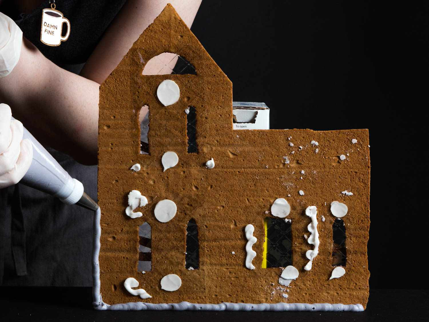Piping lines and dollops of royal icing onto a wall of gingerbread to begin assembling the house