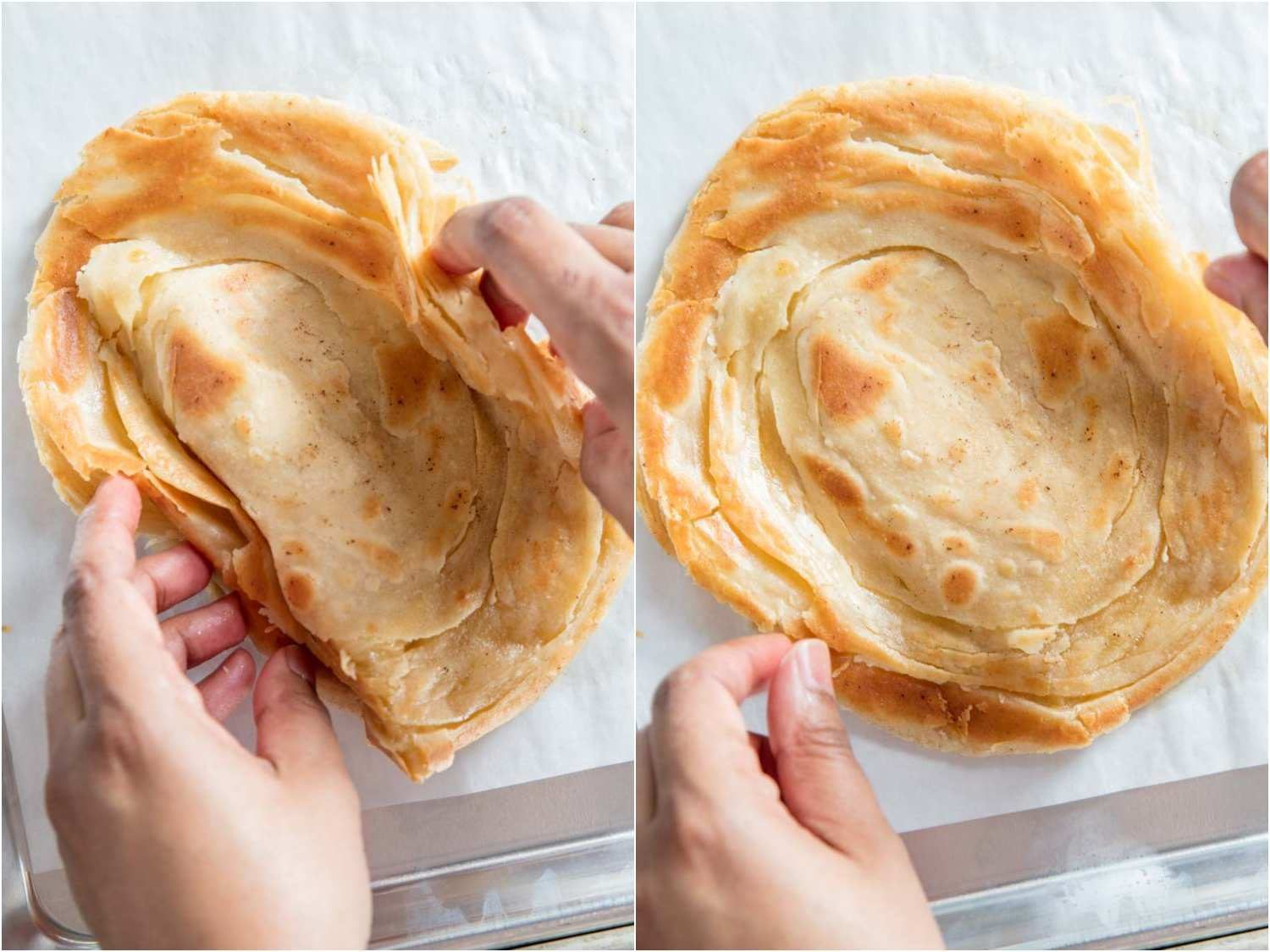 Two hands on the sides of a cooked paratha, scrunching it gently to release steam