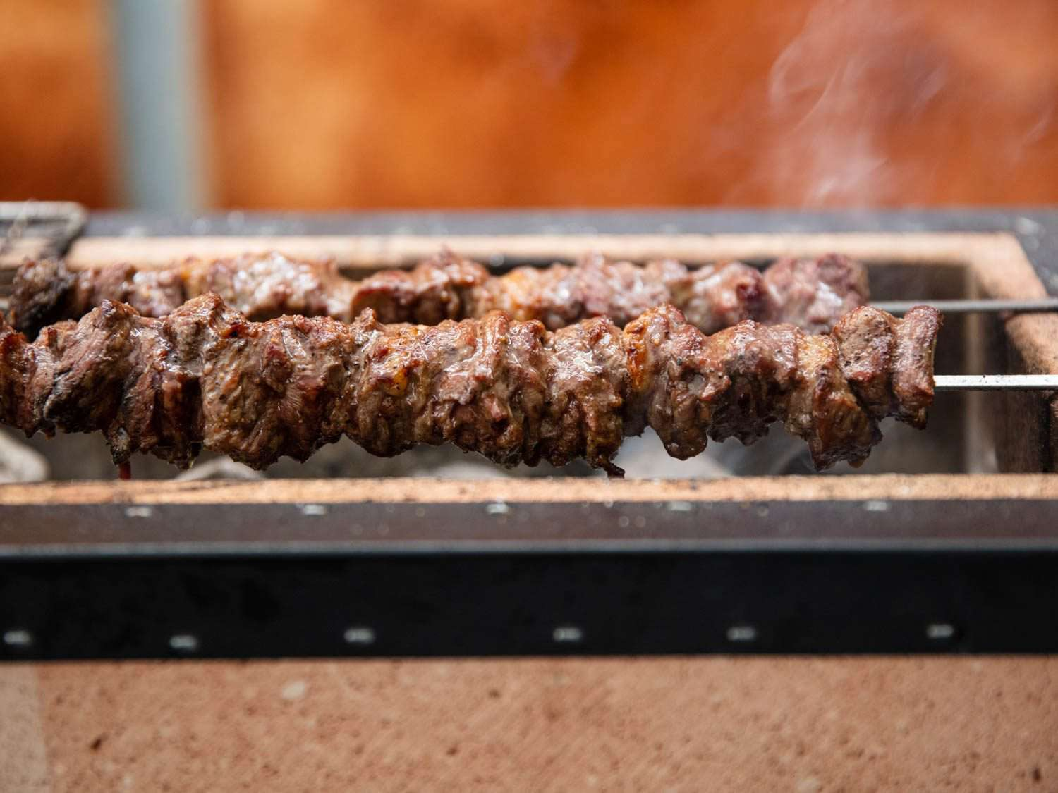 Side view of lamb skewers grilling over coals on a Japanese konro grill