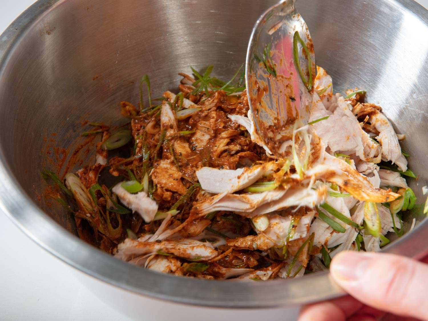Mixing turkey together with dressing and sliced scallions in a mixing bowl.