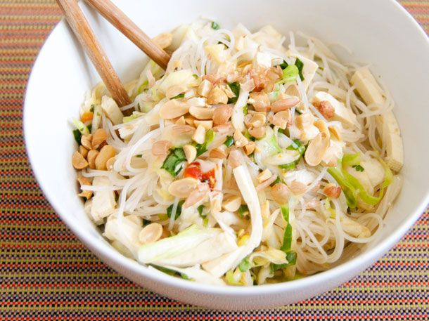 A white bowl of spicy rice noodle salad with sliced cabbage, peanuts, and tofu