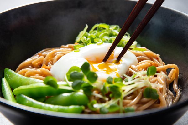 A bowl of mazemen with sugar snap peas, and chopsticks are breaking the yolk of the poached egg on top.