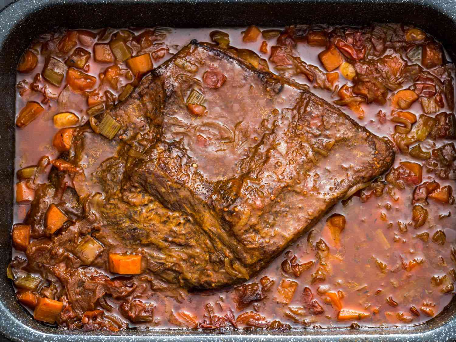 Overhead shot of a Jewish-style braised brisket in a sauce of carrots and onions