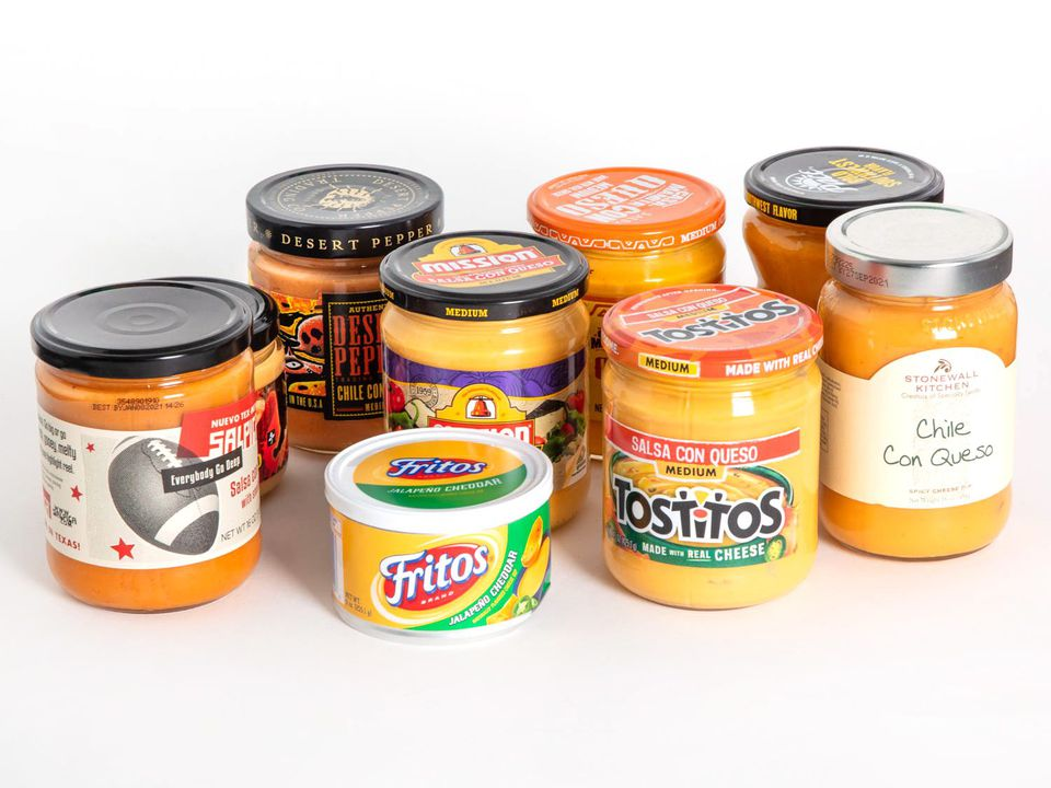 A group of nine queso dips in jars against a white background.
