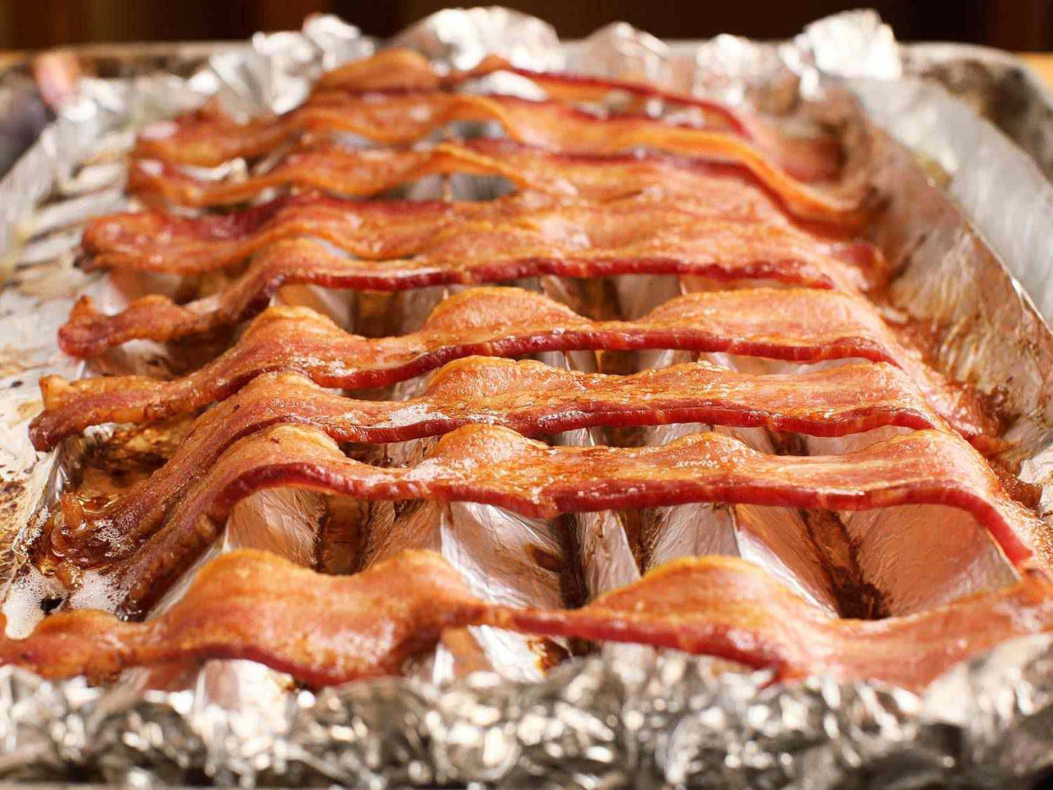 Close-up of strips of bacon on a pan lined with a corrugated piece of aluminum foil