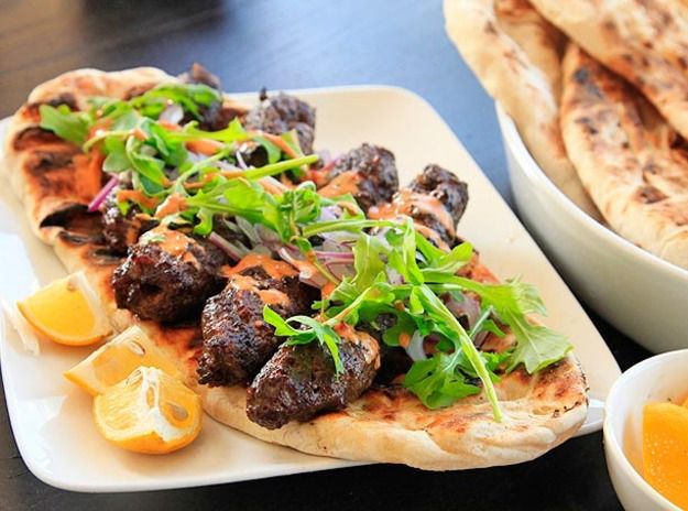 Kofte (minced-lamb) kebabs laid out on flatbread, topped with spicy harissa-yogurt sauce and arugula