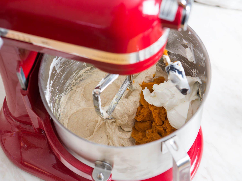 Adding pumpkin puree and sour cream to stand mixer bowl of cheesecake mixture to make pumpkin cheesecake.