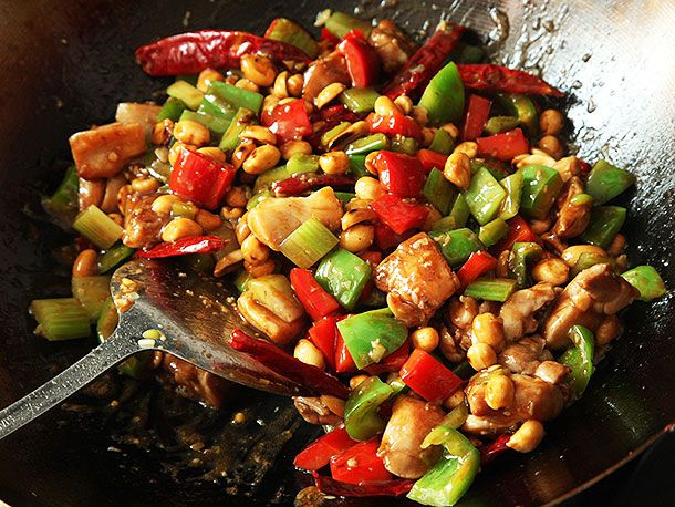 Adding sauce and chicken to stir-fried peppers, celery, and peanuts in a wok for takeout-style kung pao chicken.