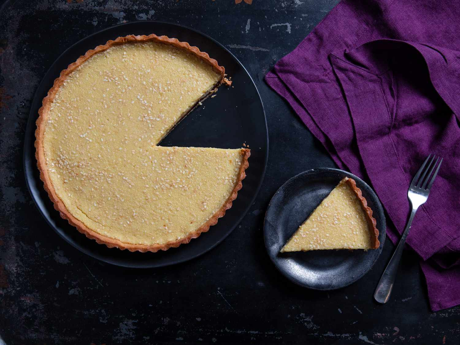 an overhead shot of a slice of toasted white sesame tart with bittersweet chocolate ganache next to the full tart