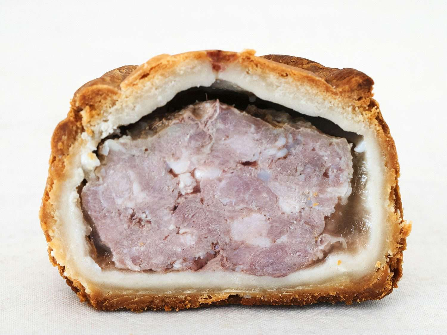 Interior of a Melton Mowbray pork pie, showing the meat filling, layer of jelly, and pastry crust outside