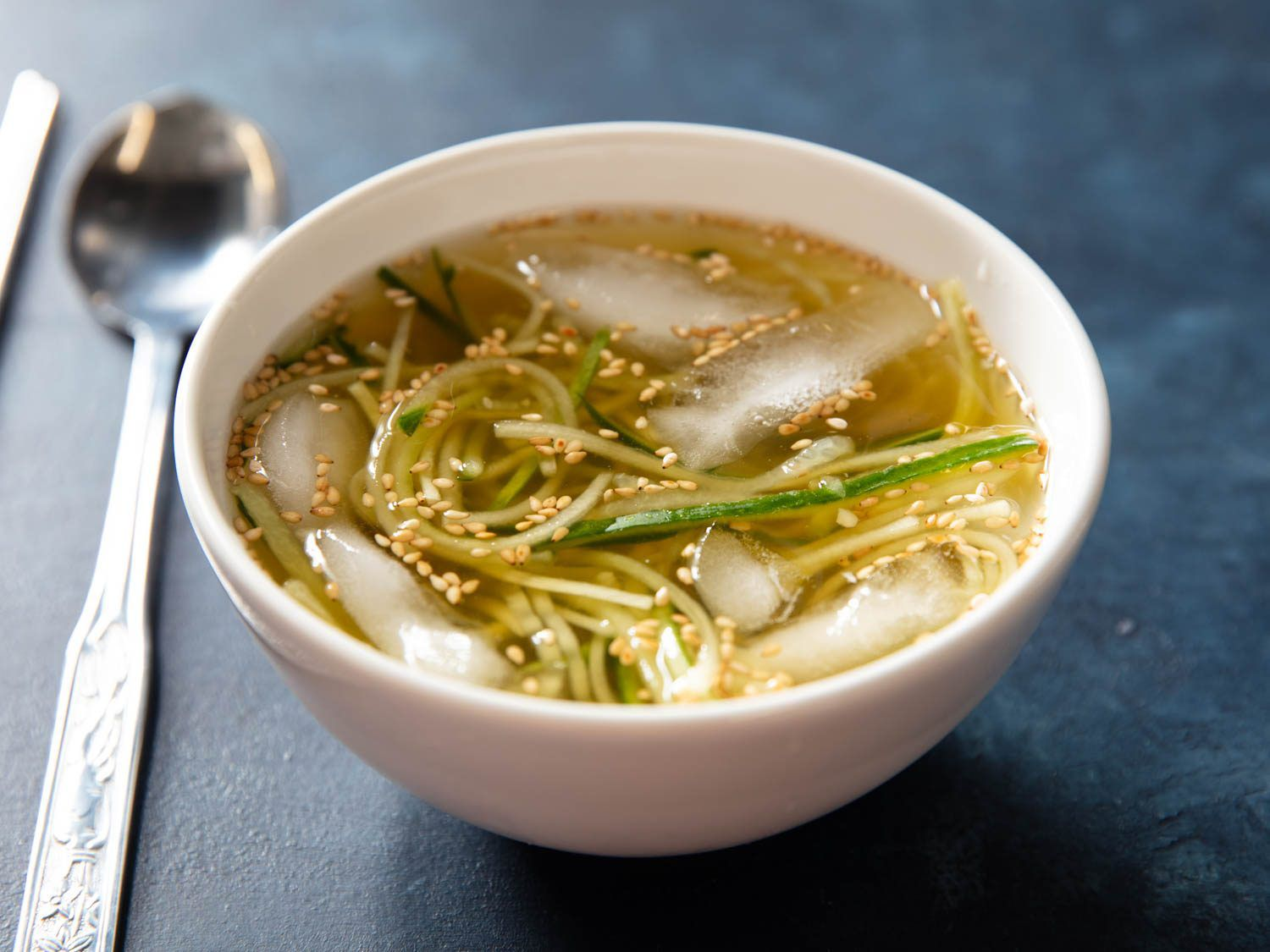 A bowl of oi naengguk, an icy chilled korean soup, will ice cubes floating in the bowl with the cucumbers and broth