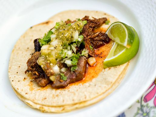 Smoked lamb barbacoa tacos on corn tortillas with lime wedges and salsa verde.
