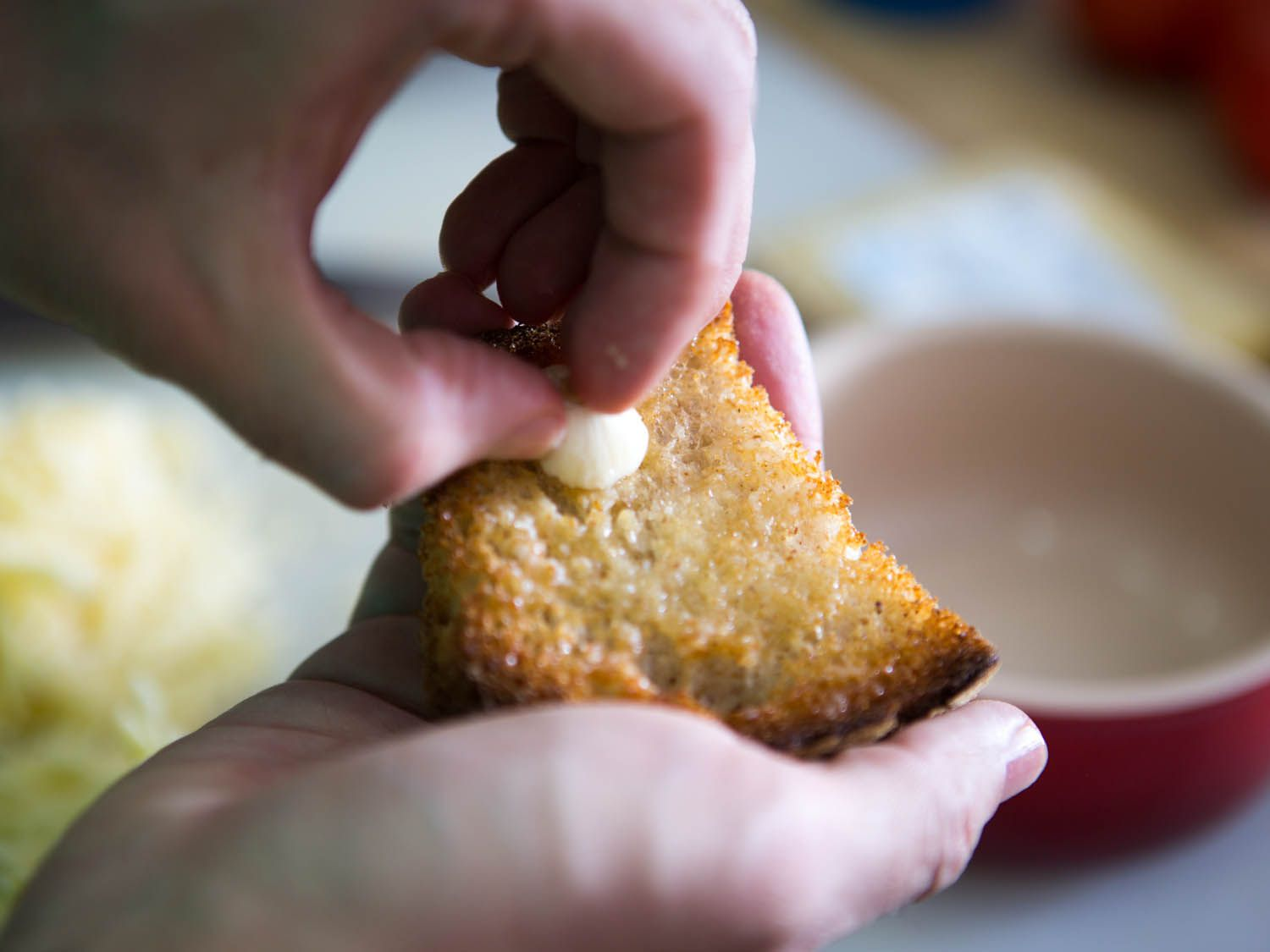 Rubbing a piece of toast with garlic before using it to top French onion soup.