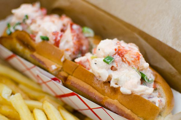 Lobster rolls in a basket next to some French fries.
