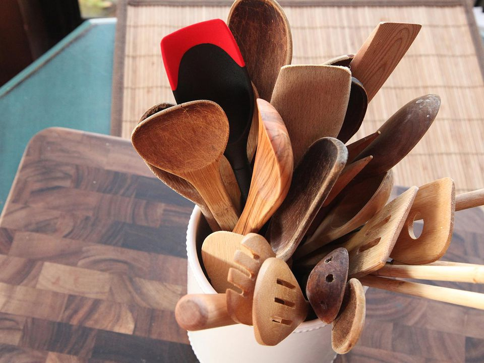A utensil crock full of wooden and nylon spoons and spatulas